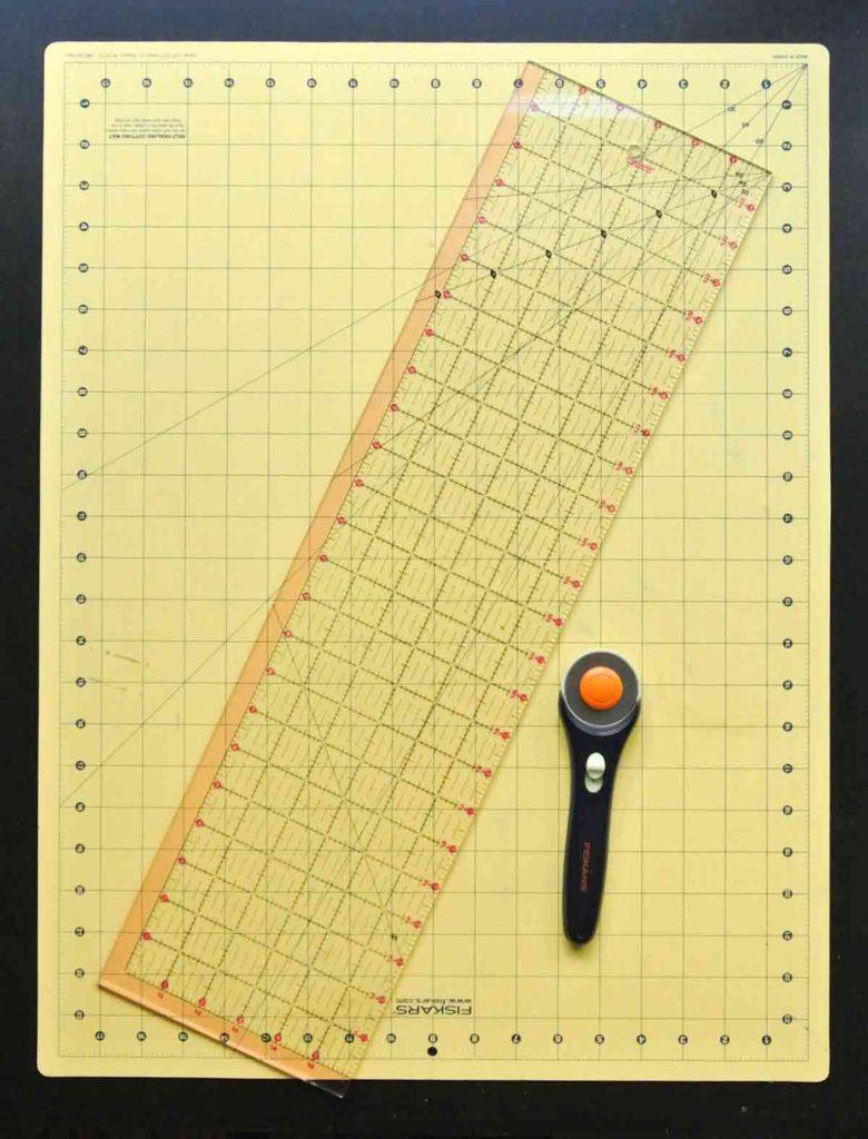 Rotary Cutter Vs Scissors A beginner's Guide. Shows Rotary cutter, a cutting mat, and clear plastic ruler