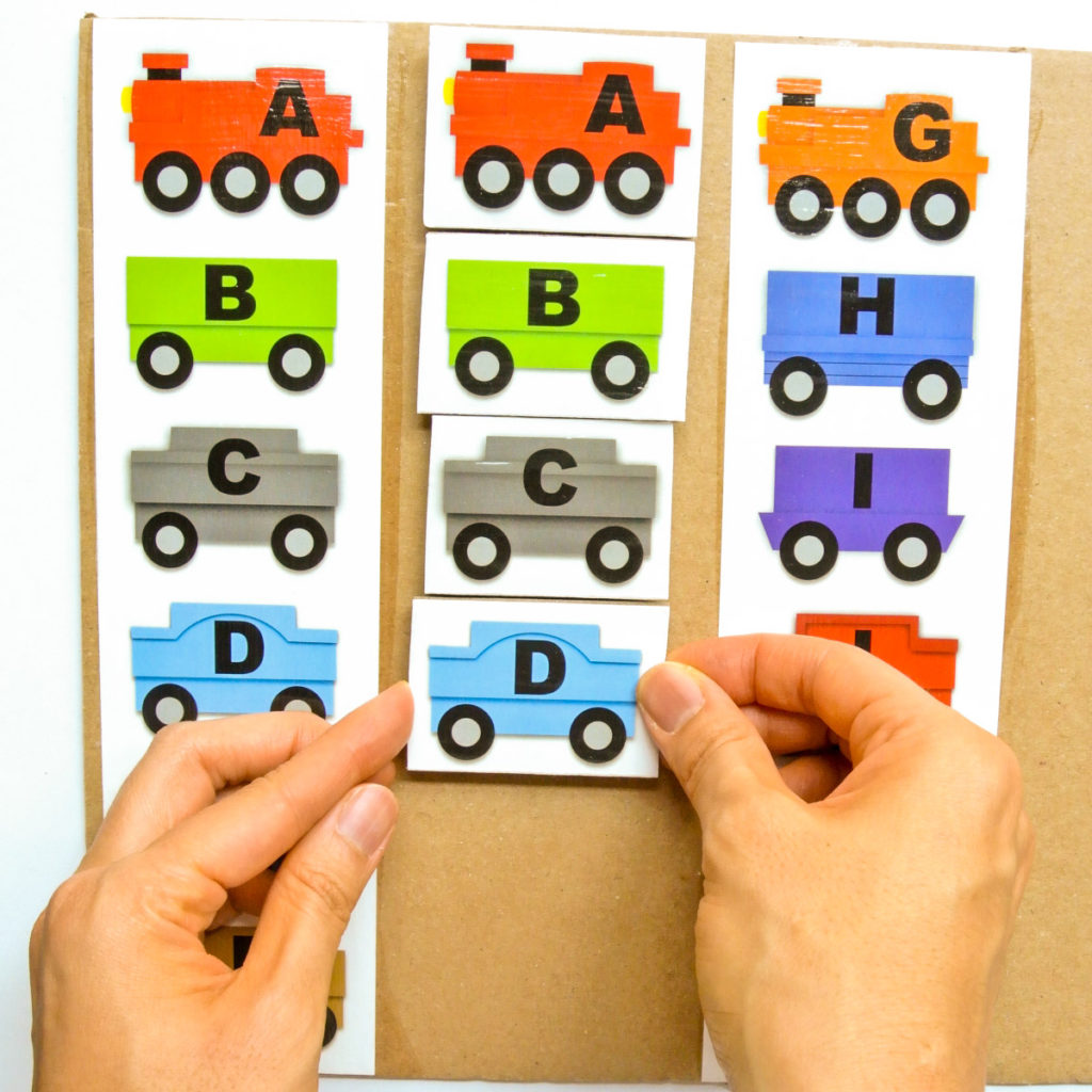 Sticking ABC Train piece with velcro onto Cardboard for ABC Matching Train Activity