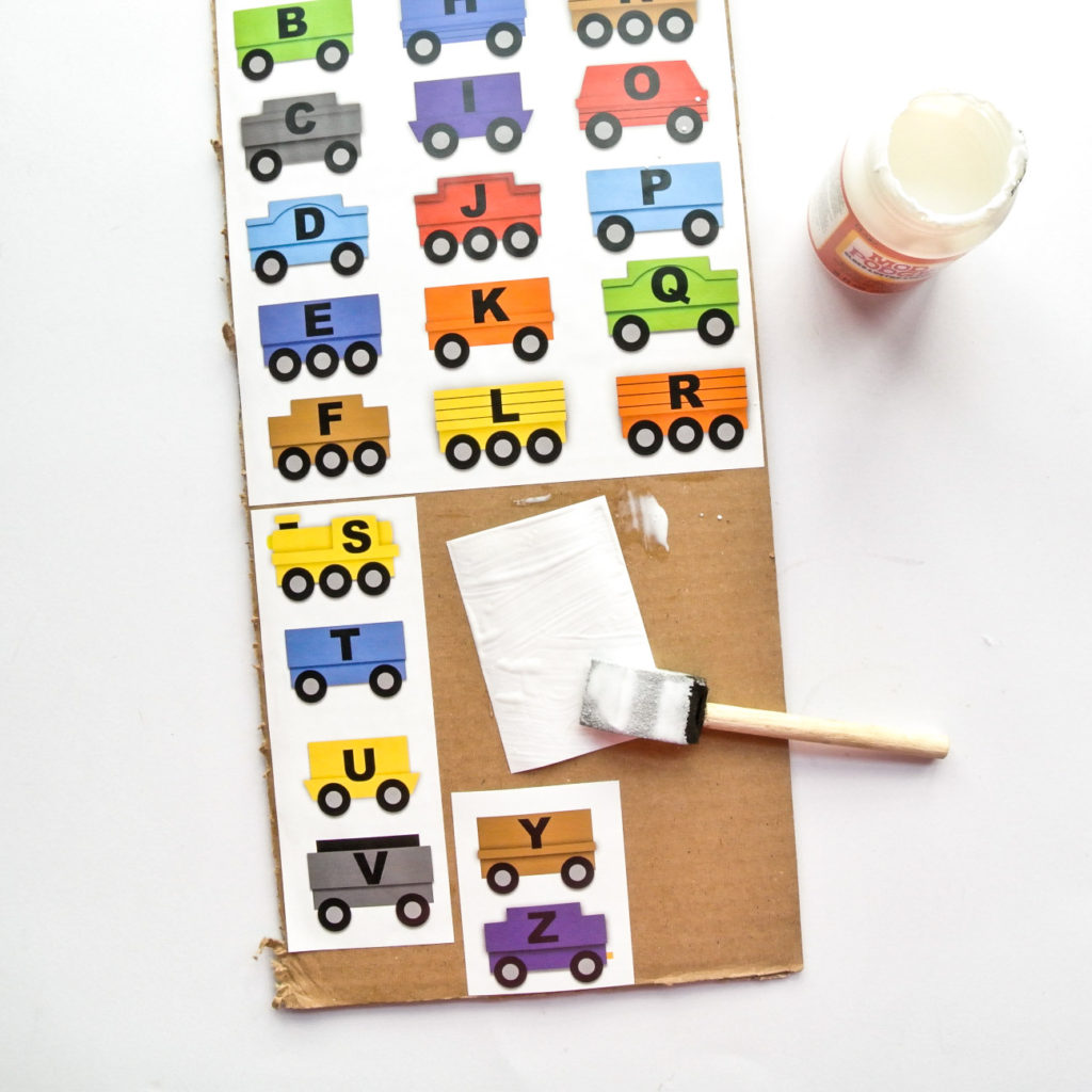 Gluing ABC Train Pieces to Cardboard with Modpodge