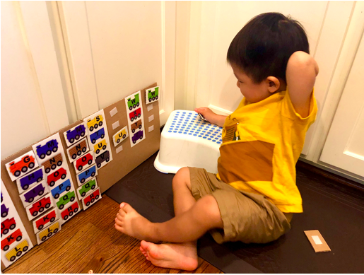 Toddler trying to figure out where to put train pieces on ABC Letter matching Train Activity
