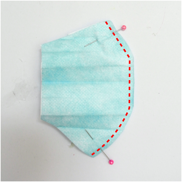 Shows toddler surgical mask pinned at the midline with red dotted lines showing where to sew at the midline