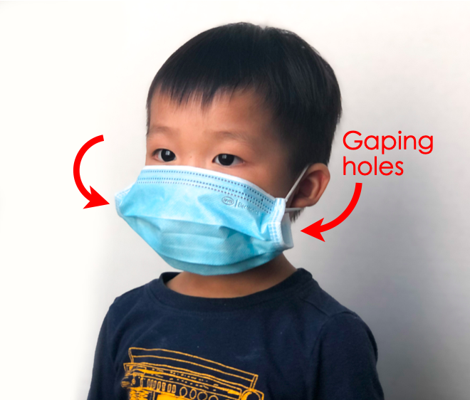 """Shows toddler wearing ill fitted adult surgical mask. Red arrows point to side of mask in front of ear loop with text """"gaping holes"""""""