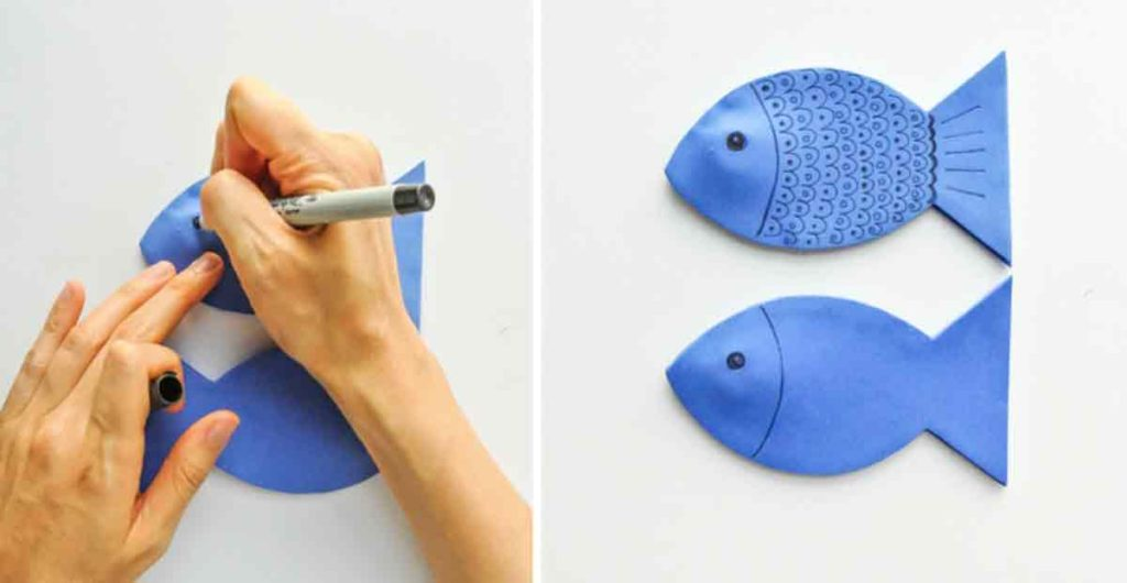 Shows hands decorating blue foam fish with black permanent sharpie pen for DIY Magnetic Fishing Game