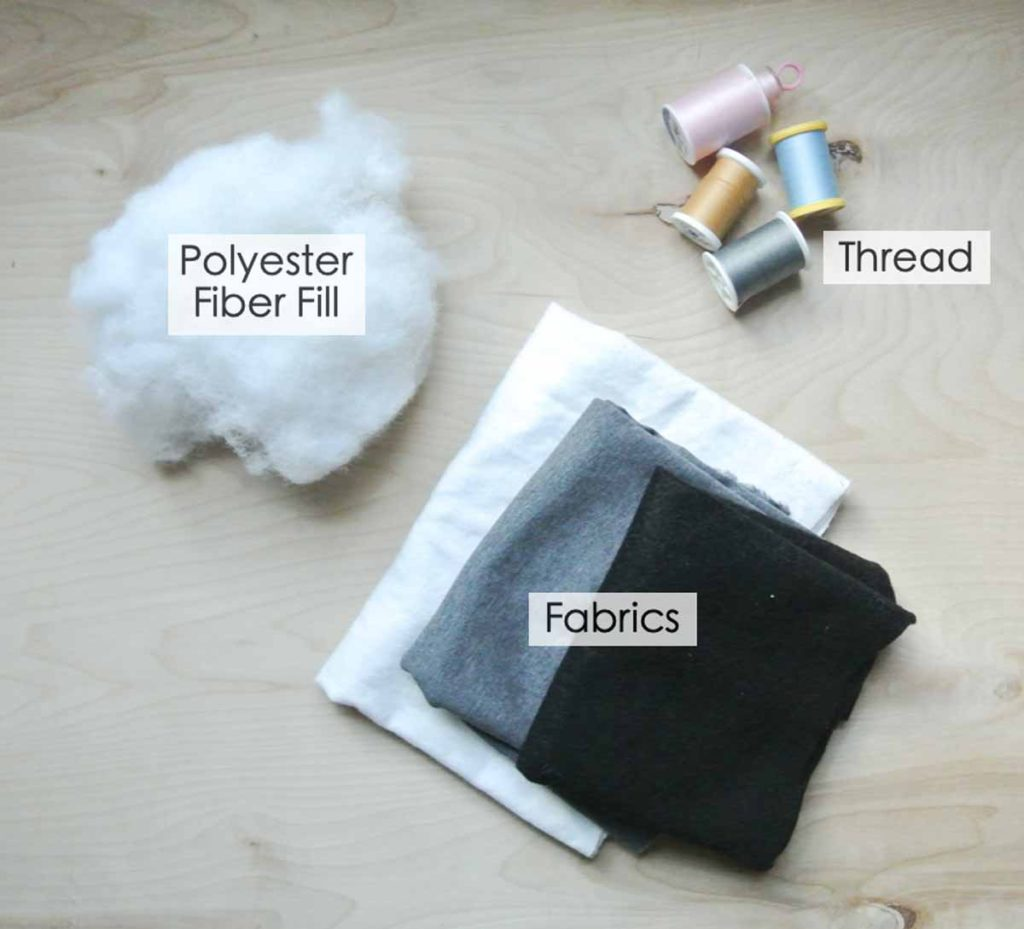 Shows basic materials for making plush doll: Polyester fiber fill, threads, and fabric