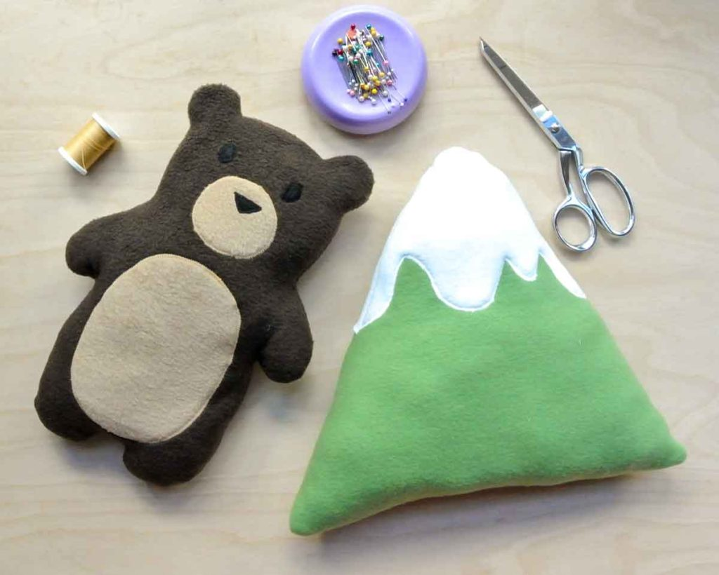Shows Finished DIY Bear and Mountain Plushie with scissors, pins, and thread. How to Make a Plushie Tutorial
