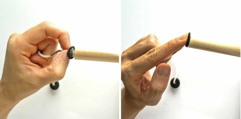 Hands applying black felt cirlce and thread to end of wooden rod to make magnetic fishing rod for kids