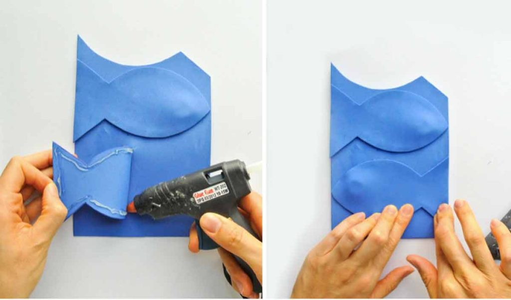 Shows hands and glue gun gluing rest of magnetic foam fish together for DIY Magnetic Fishing Game