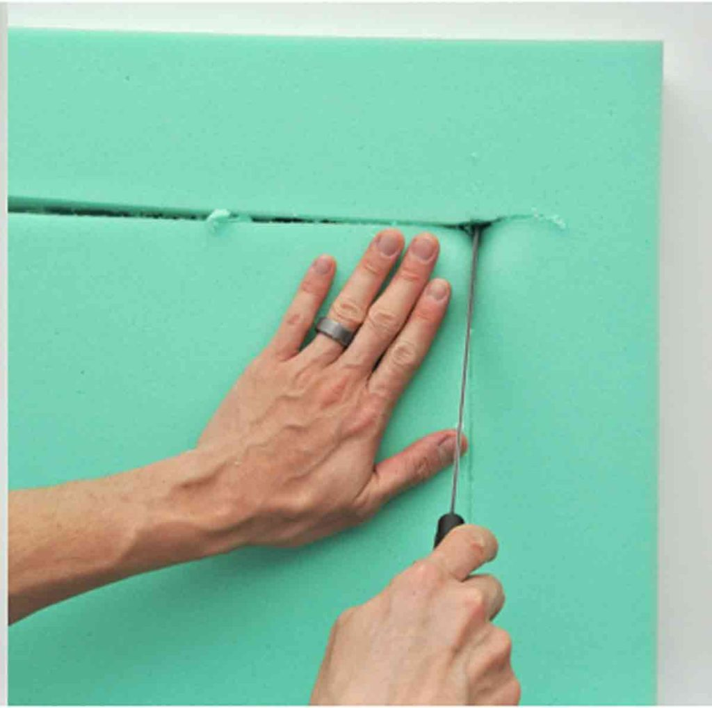 Shows Hand using Bread Knife to Cut Foam for makig square bar stool cushion with ties