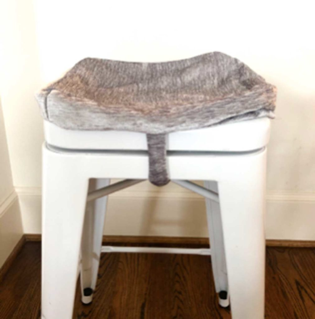 Shows bar stool cushion cover tied on over bar stool