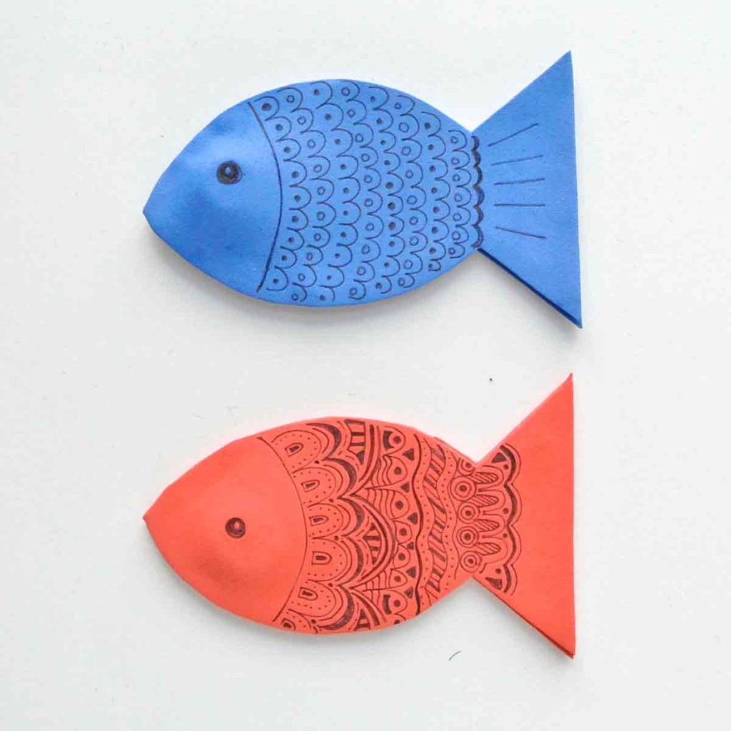 Shows Blue and red magnetic foam fish decorated with black sharpie markers
