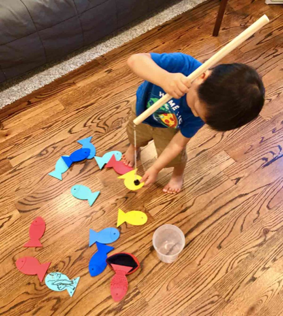 Shows Toddler holding magnetic fishing rod playing with homemade magnetic fishing game