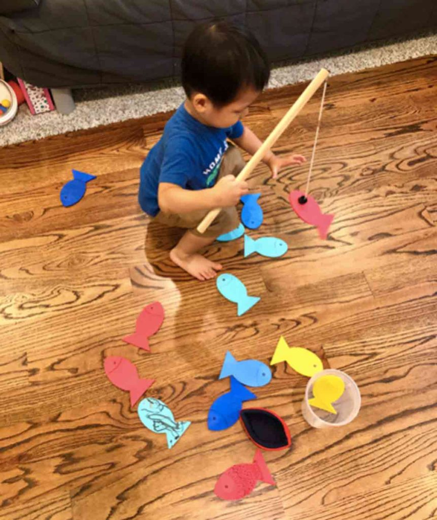 Shows toddler playing with homemade DIY magnetic fishing game