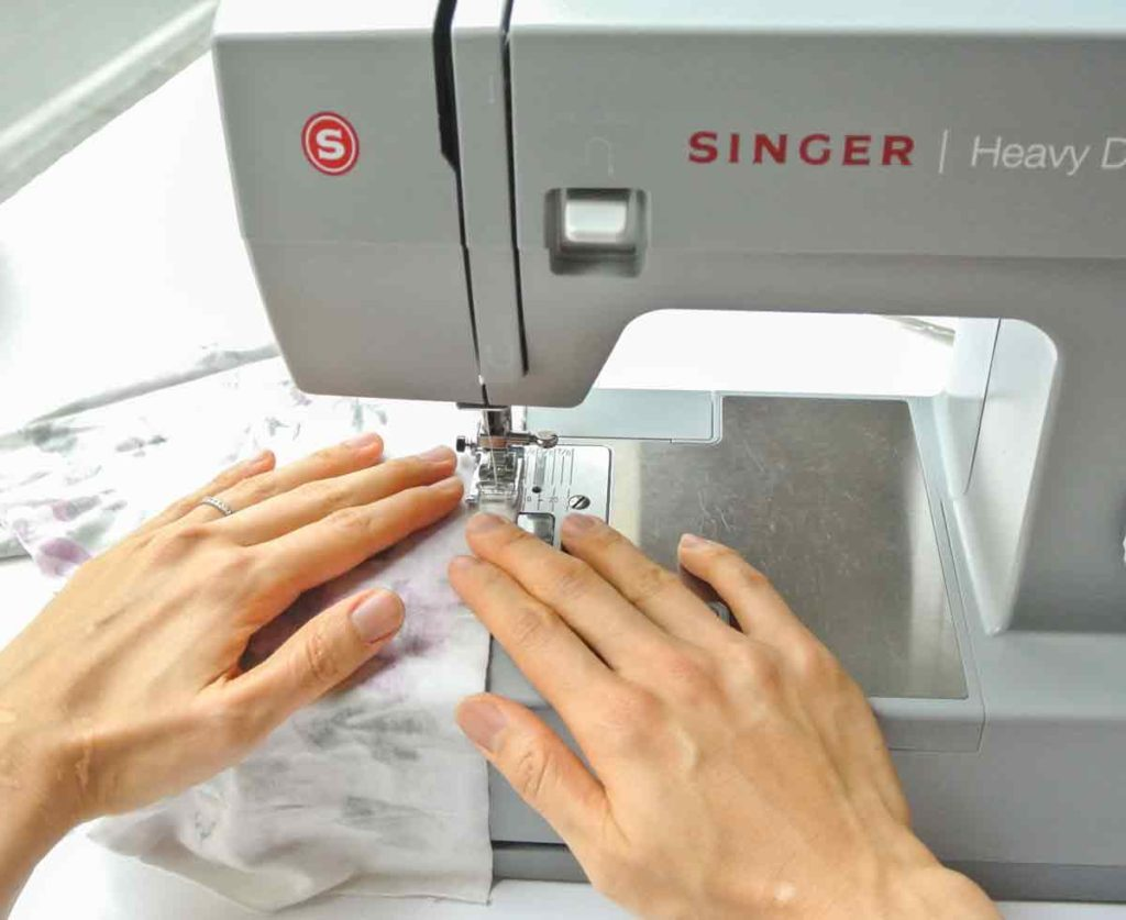 How to sew Knit fabric using hands to gently guide fabric into machine as you sew