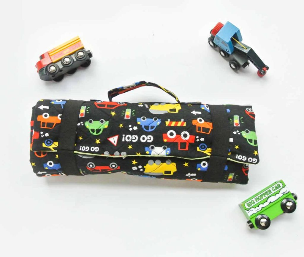 DIY Toy Car Playmat Carrier case rolled up with toy vehicles next to it.