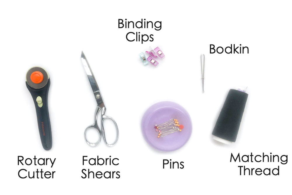 How to Make Drawstring Shoe Bag Materials. Shows rotary cutter, fabric shears, pins, matching thread, bodkin, and binding clips