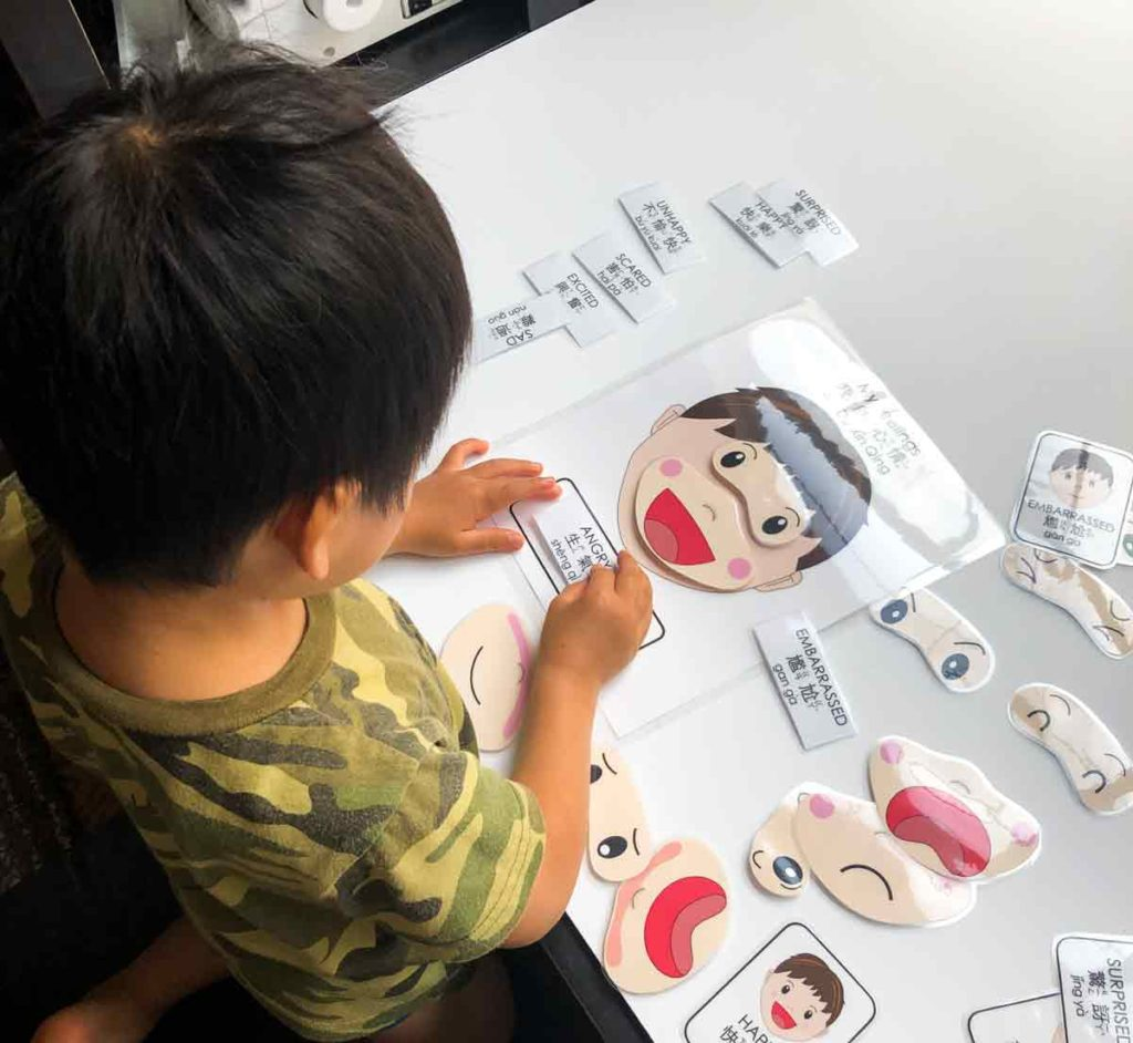 Toddler playing with Free Printable Emotions Matching Activity in Bilingual English and Chinese