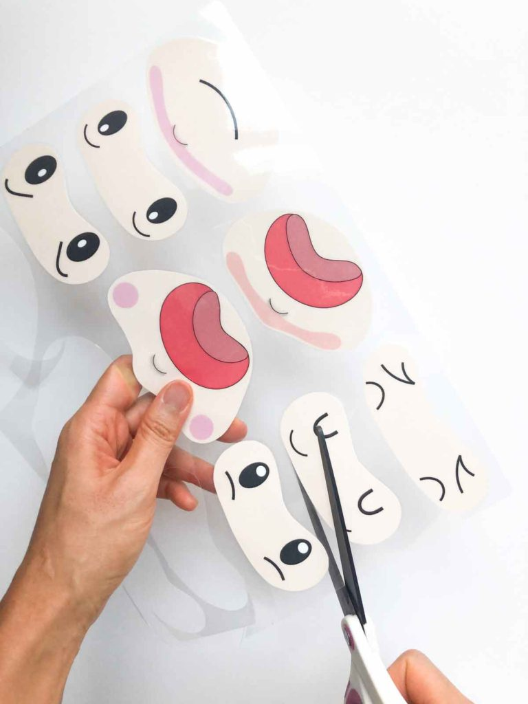 Shows hands cutting out laminated facial expressions of kids' emotions activity free printable