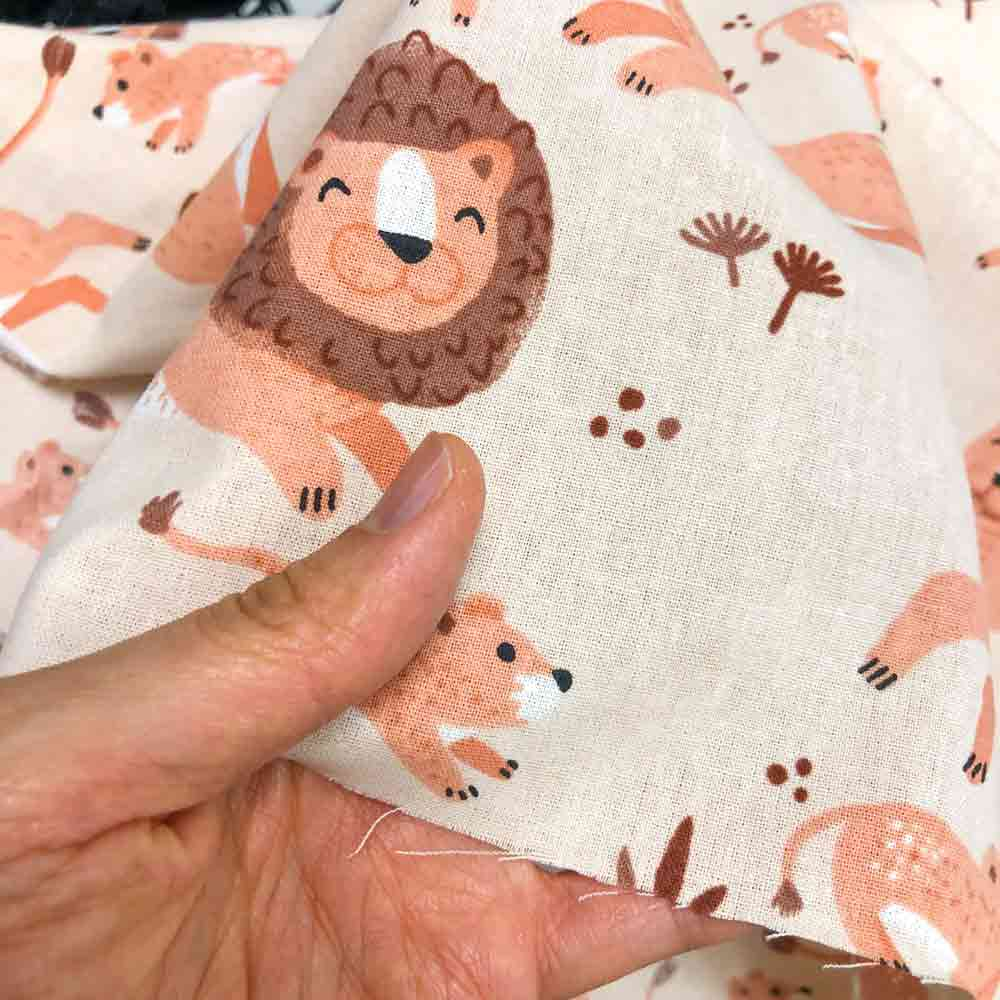 what fabric is best for baby bibs. Hand holding 100% printed cotton fabric up close image